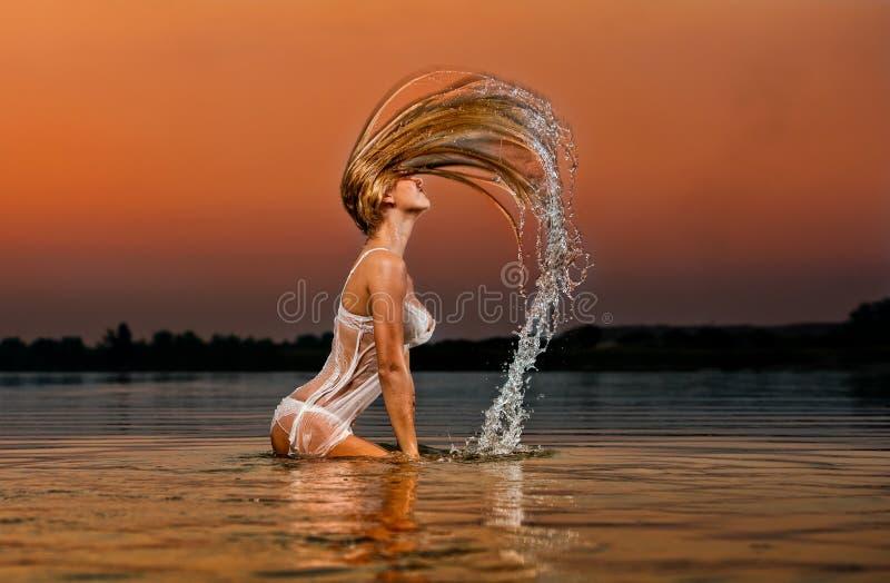Sexy blonde vrouw in water bij zonsondergang stock fotografie