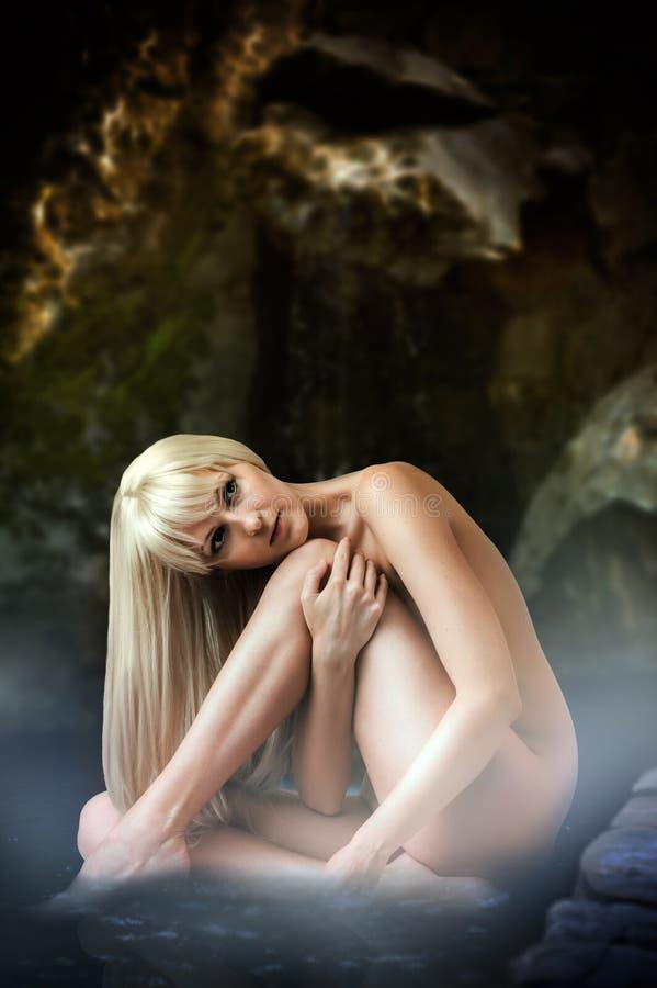 Sexy blonde vrouwenzitting in lagunewater royalty-vrije stock afbeeldingen