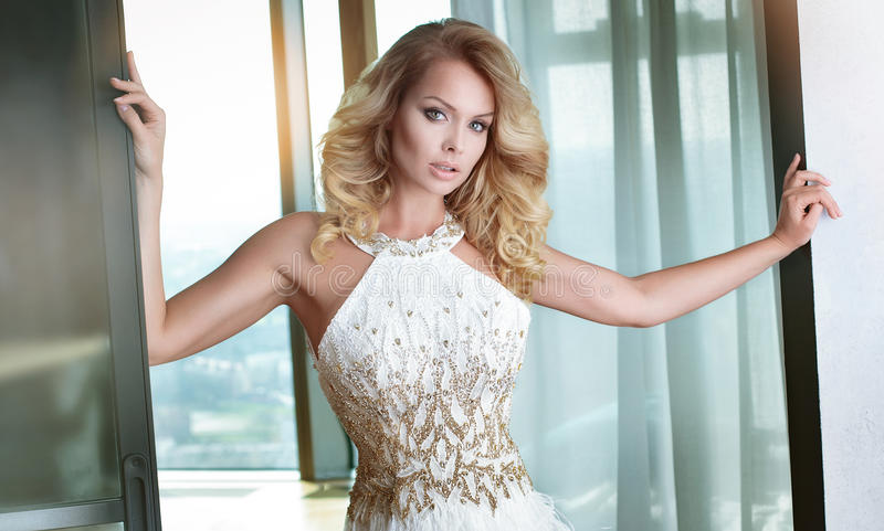 Blonde woman in elegant dress. Elegant blonde caucasian woman posing in beautiful dress royalty free stock photo