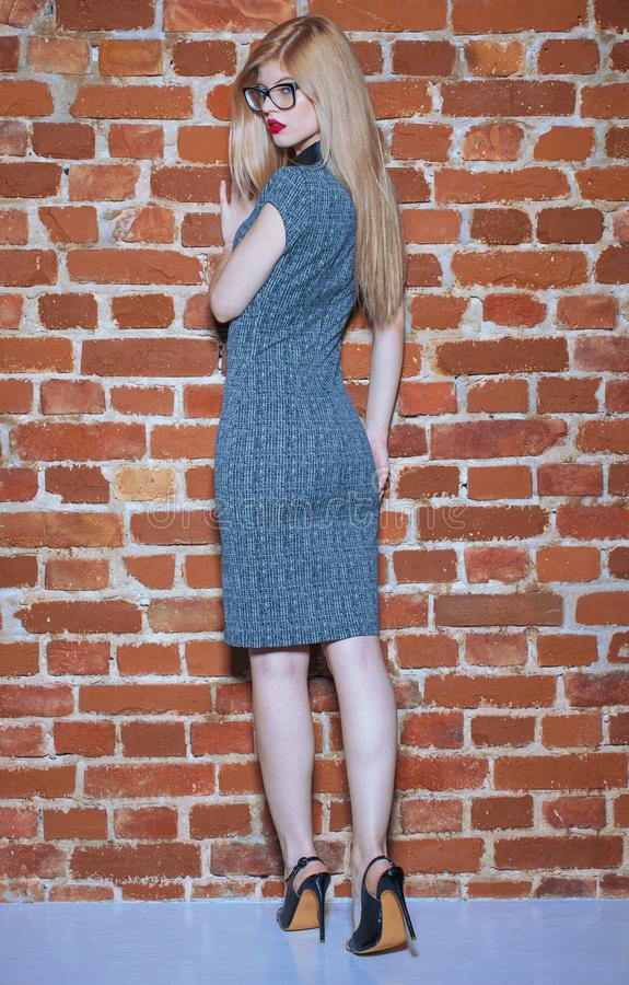 Sexy blonde woman in eyeglasses looking back at wall. Sexy young blonde woman in eyeglasses looking back at wall stock photography