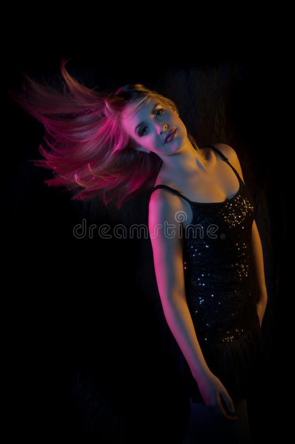 blonde woman flicking her her in colored lights against a black background stock photography