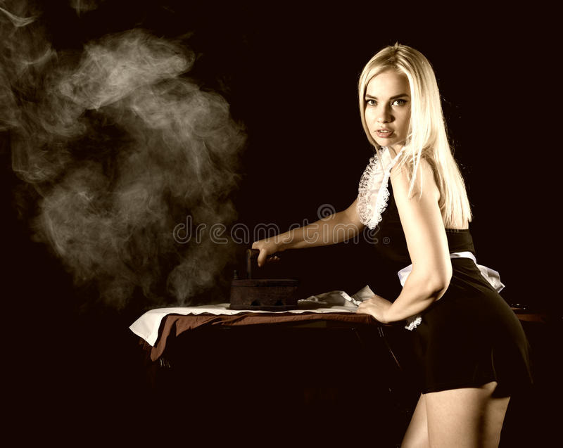 Blonde woman in housekeeper suit, ironing white shirt with old iron. retro style on a dark background. Back view of blonde woman in housekeeper suit, ironing royalty free stock photos