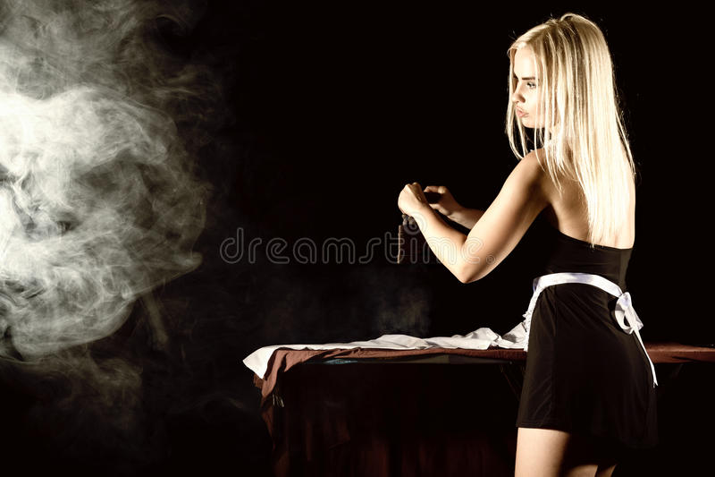 Blonde woman in housekeeper suit, ironing white shirt with old iron. retro style on a dark background. Blonde woman in housekeeper suit, ironing white shirt with royalty free stock photography