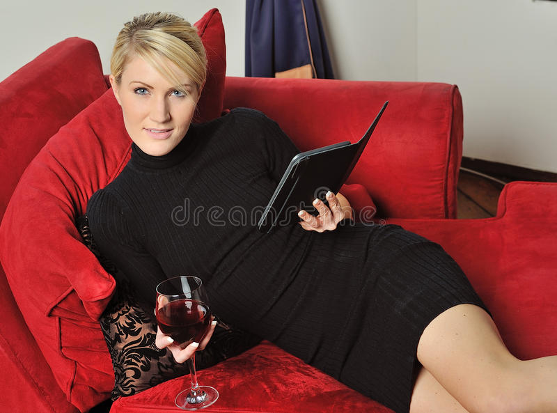 Blonde Woman Reading An E-reader With Wine Stock Images