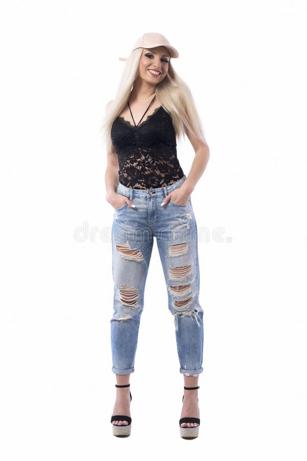 Sexy blonde young adult caucasian woman in trendy look with hands in pockets smiling at camera royalty free stock image