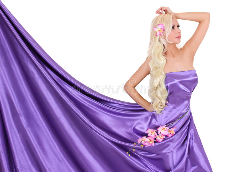 blonde young woman in purple silk dress with flowers stock photo