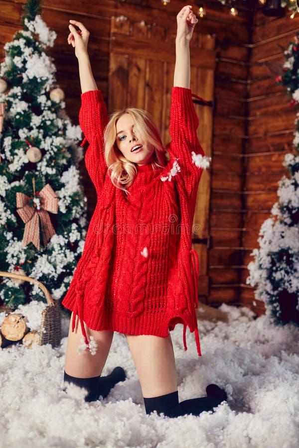Sexy blondemeisje in de rode sweater, hebbend pret en stellend tegen de achtergrond van Kerstmisdecor De winter en Kerstboom stock fotografie
