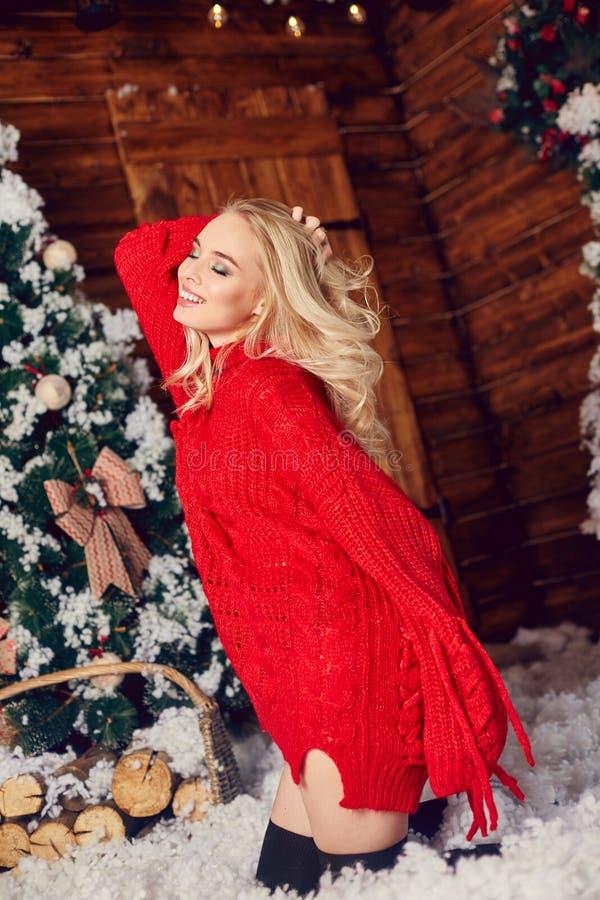 Sexy blondemeisje in de rode sweater, hebbend pret en stellend tegen de achtergrond van Kerstmisdecor De winter en Kerstboom royalty-vrije stock fotografie