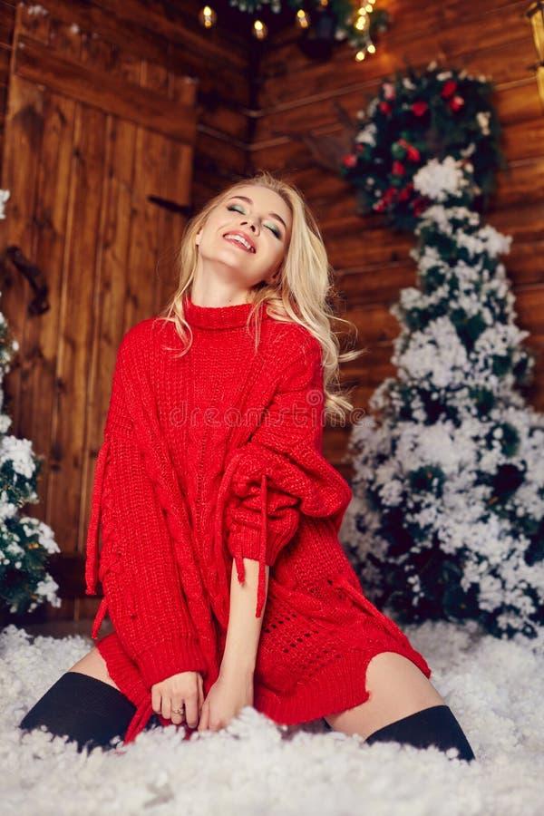 Sexy blondemeisje in de rode sweater, hebbend pret en stellend tegen de achtergrond van Kerstmisdecor De winter en Kerstboom royalty-vrije stock foto's