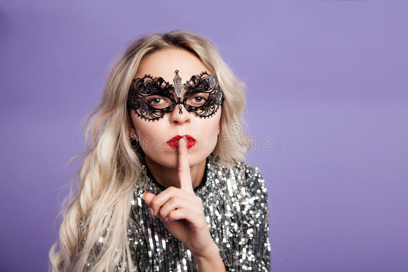 Sexy blondes Mädchen in der Spitzemaske setzte einen Finger zu ihren Lippen Raum für Text lizenzfreie stockfotos