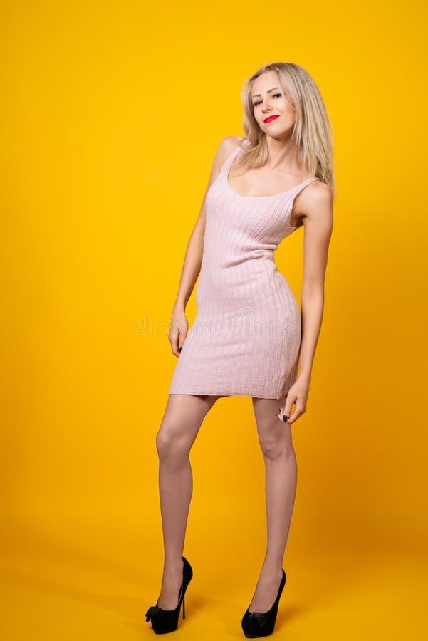 Sexy blondes Mädchen wirft auf dem gelben Hintergrund auf, der rosa kurzes Kleid trägt lizenzfreies stockbild