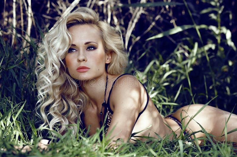 Sexy blondevrouw die in wildernis liggen stock afbeelding