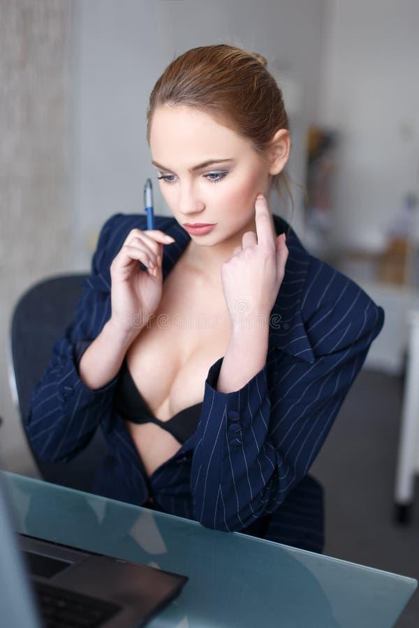 Sexy blondevrouw in glazen online flirt in bureau stock afbeelding
