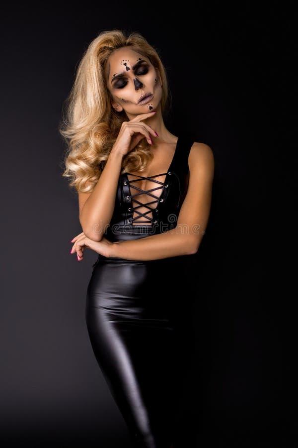 Sexy blondevrouw in Halloween-make-up en leeruitrusting op een zwarte achtergrond in de studio Skelet, monster stock fotografie