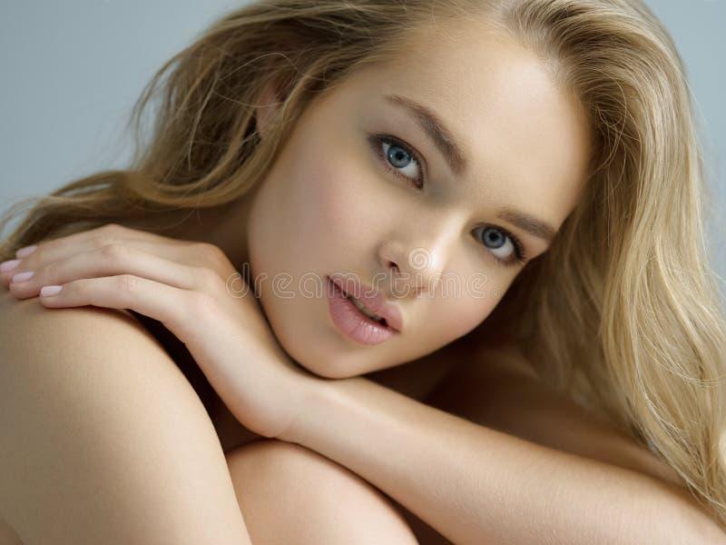 Sexy blondevrouw met lang krullend haar stock fotografie