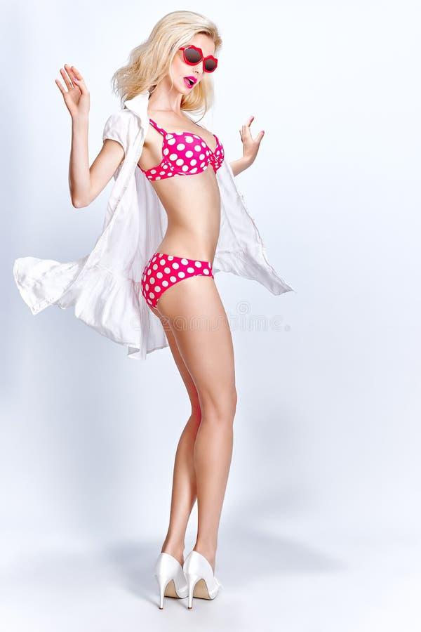 Sexy blondevrouw in rood puntenzwempak en stock foto's