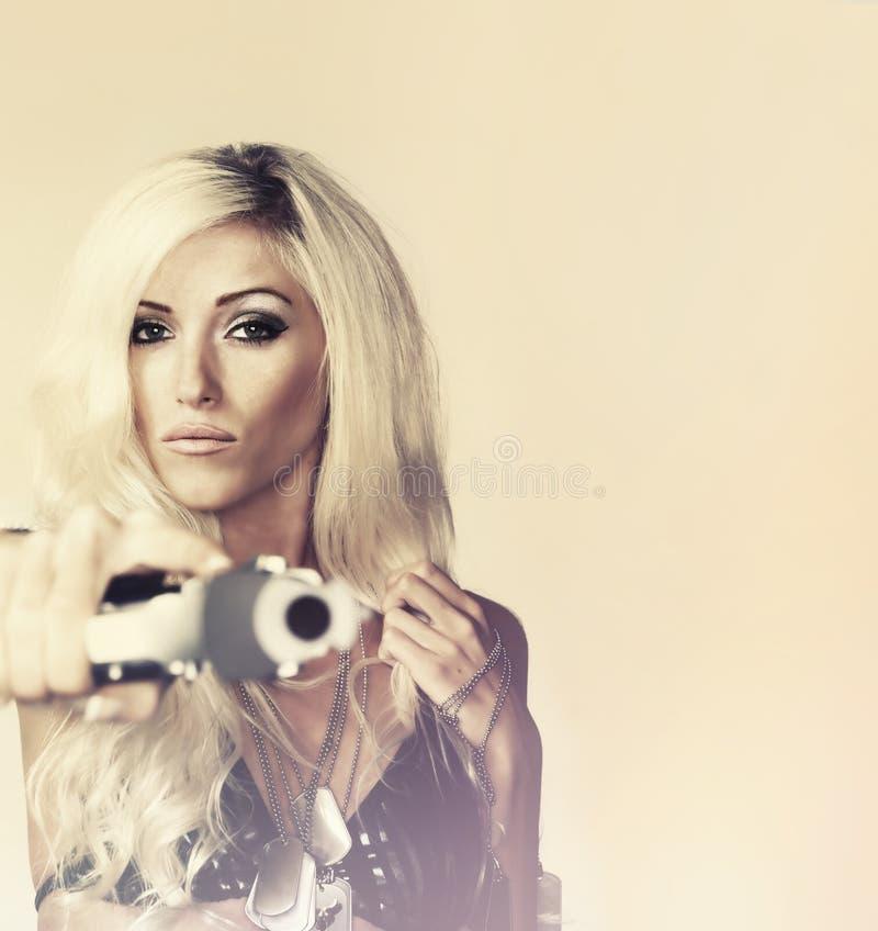 Sexy Blondine, die Gewehr halten stockbilder