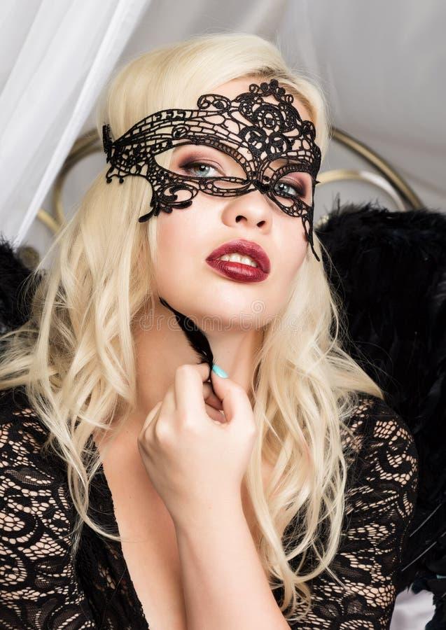 Sexy Blondine in einer Spitzemaske, die eine schwarze Feder nahe ihrem Gesicht hält stockfotografie