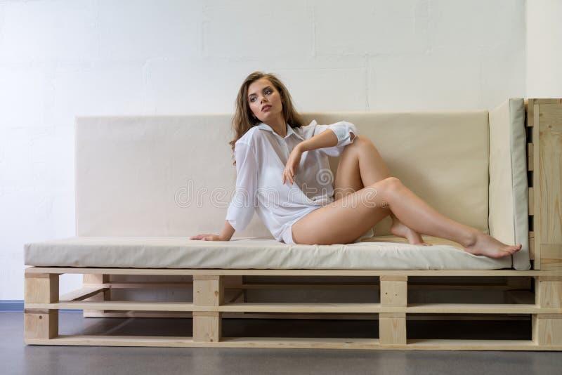 Sexy Blondine im Hemd, das auf Sofa aufwirft stockbilder