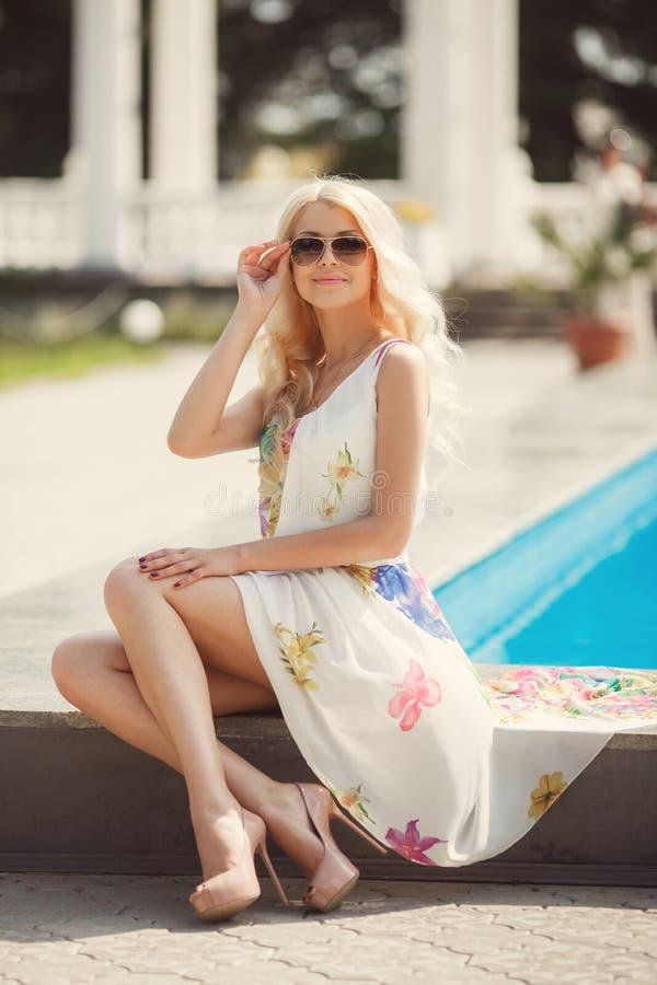Sexy Blondine sitzt Poolside mit blauem Wasser stockbild