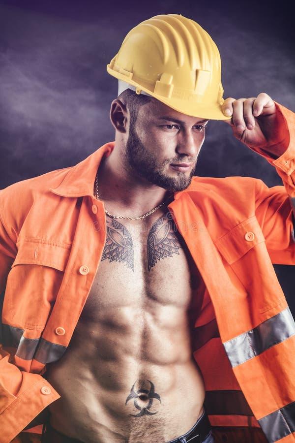 Sexy bouwvakker met oranje kostuum open op naakt torso stock afbeelding