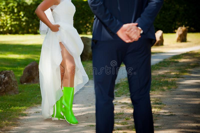 Wedding in green rubber boots and white dress stock photos