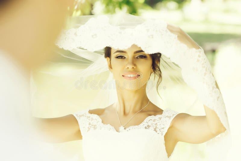Pretty bride under veil stock photography