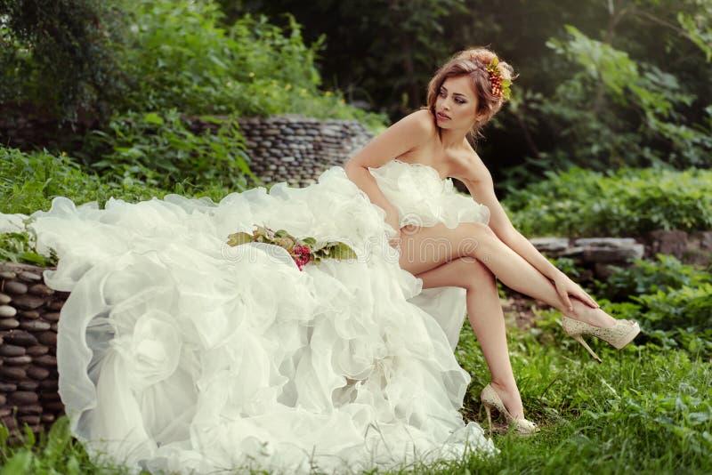 Sexy bruidvrouw met lange benen in weelderige huwelijkskleding royalty-vrije stock fotografie