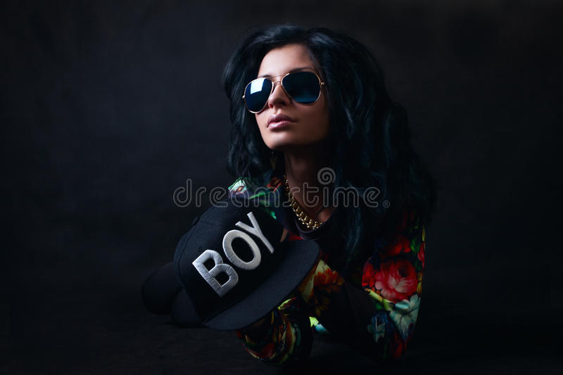 brunette in a black cap and glasses. Swag girl. Fashion stock images