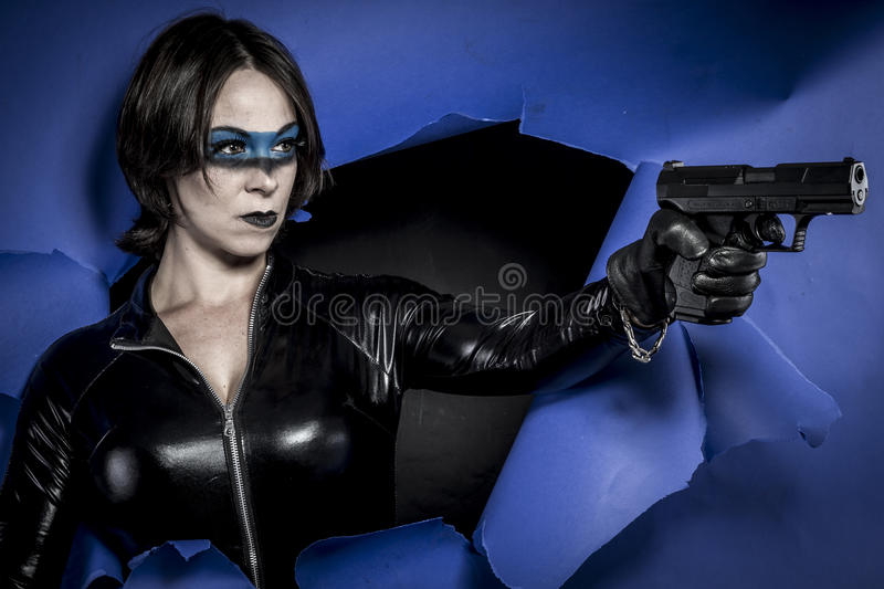 Sexy, Brunette in black latex costume with pistol over broken pa. Brunette with black latex dress stock photo