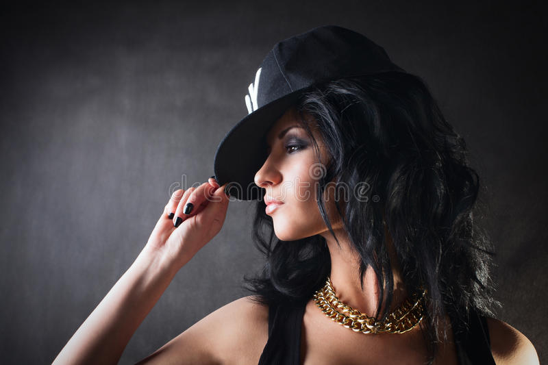 brunette in cap. Swag girl. Fashion stock image
