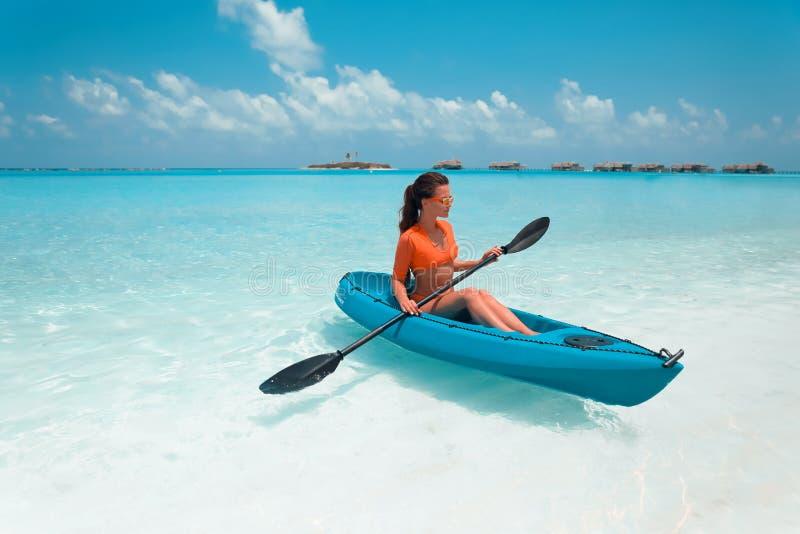 Sexy Brunette, der einen Kajak schaufelt Frau, die ruhige tropische Bucht erforscht maldives Sport, Erholung Sommerwassersport, A lizenzfreie stockfotos