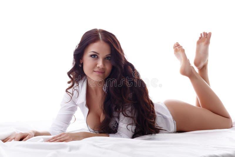 Sexy brunette die camera bekijken terwijl het liggen in bed stock foto