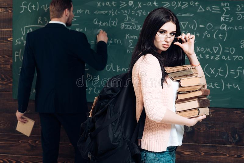 brunette female student holding her glasses while carrying pile of books. Young college girl in pink cardigan royalty free stock images