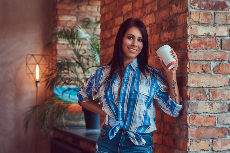 A brunette in a flannel shirt and jeans holds a cup of coffee posing against a brick wall. stock photography