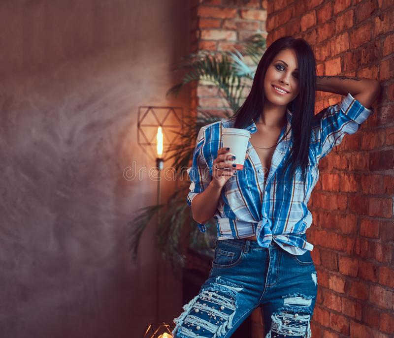 A brunette in a flannel shirt and jeans holds a cup of coffee posing against a brick wall. stock images