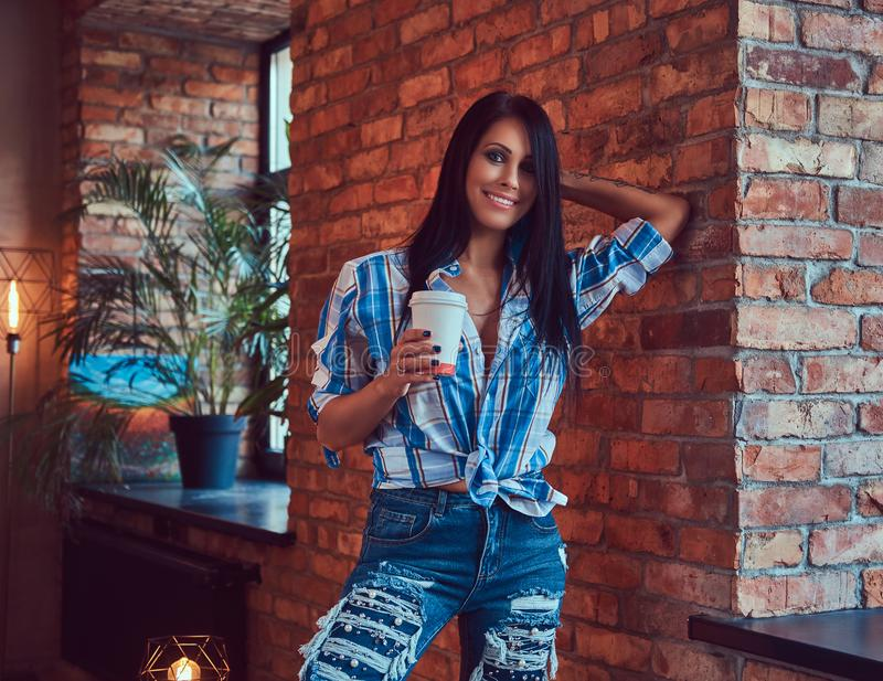 A brunette in a flannel shirt and jeans holds a cup of coffee posing against a brick wall. stock image