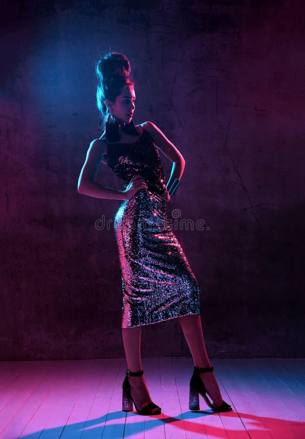 Sexy brunette Frau der schönen Mode, die in Mode im blauen und rosa Scheinkleid des Neonlichtes Goldauf Dunkelheit aufwirft lizenzfreie stockfotos