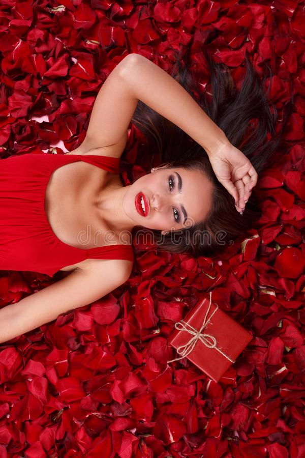 A girl in a red dress, lies in the rose petals near a gift box and holds her hand near the head. stock image