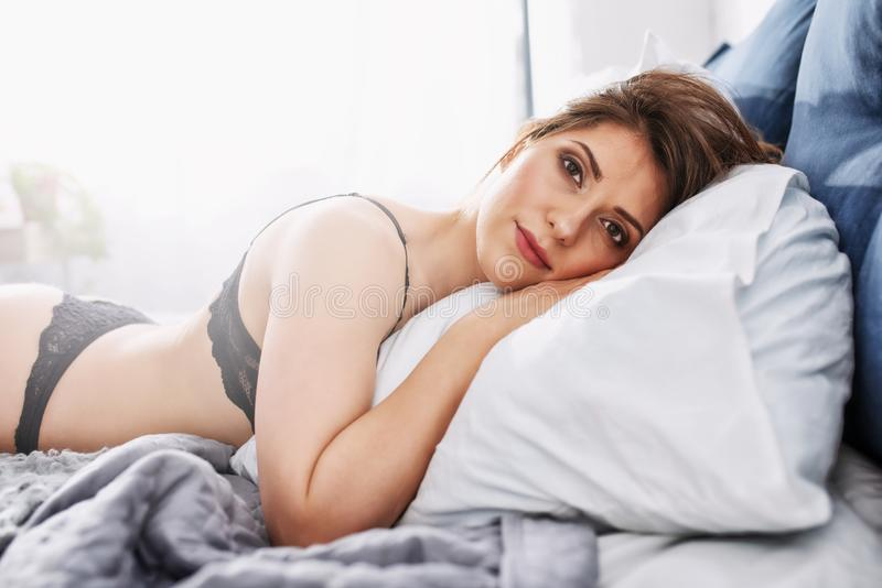 Sexy girl relaxing on the bed during morning. Concept of relax and rest. Sexy brunette girl relaxing on the bed during morning. Concept of relax and rest stock photos