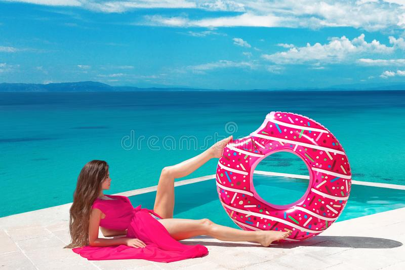 Brunette Girl relaxing with inflatable float ring by the ho. Tel infinity pool at exotic island. Travel vacation carefree woman enjoying sumer vaction. Tropical royalty free stock photo