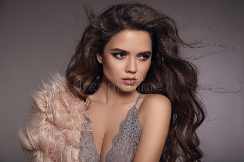 Brunette in gray lace lingerie. Fashion studio portrait of. Beautiful girl with long curly hair and evening makeup wearing in pink fur coat. Vogue style model royalty free stock image
