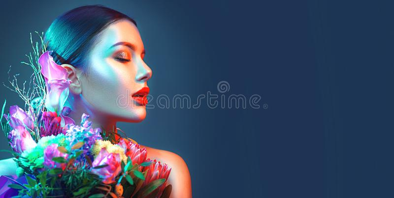 Sexy brunette model girl with bouquet of beautiful flowers. Beauty young woman with bunch of flowers in colorful neon lights royalty free stock photography
