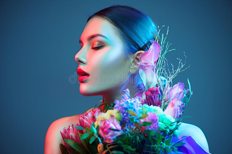 Sexy brunette model girl with bouquet of beautiful flowers. Beauty young woman with bunch of flowers in colorful neon lights. Art design royalty free stock photo