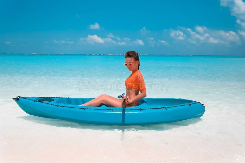 Sexy brunette paddling a kayak. Woman exploring calm tropical bay. Maldives. Sport, recreation. Summer water sport, adventure. Outdoors stock image