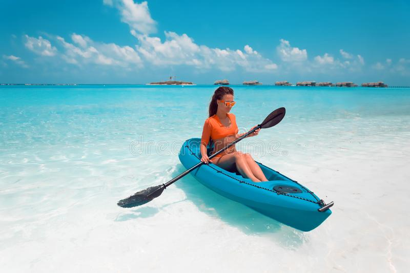 Sexy brunette paddling a kayak. Woman exploring calm tropical bay. Maldives. Sport, recreation. Summer water sport, adventure. Outdoors stock images