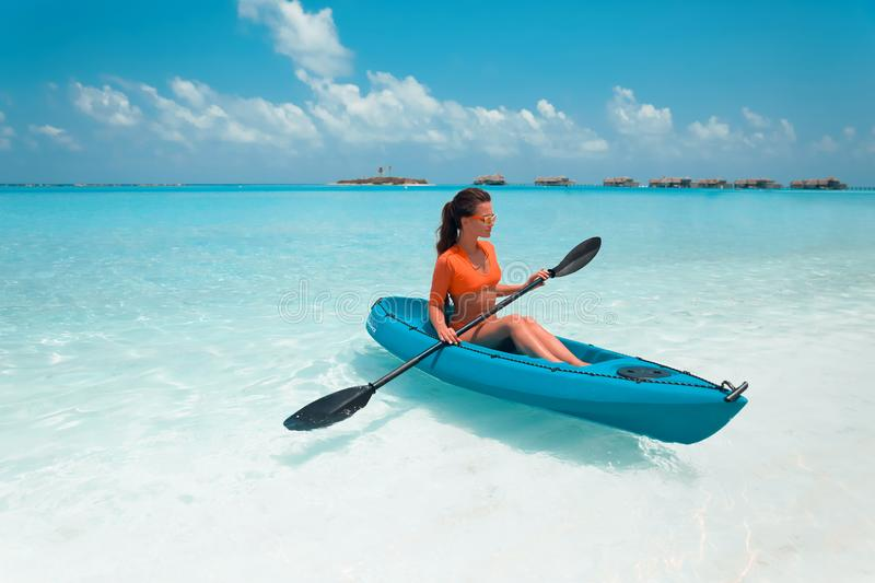Sexy brunette paddling a kayak. Woman exploring calm tropical bay. Maldives. Sport, recreation. Summer water sport, adventure royalty free stock photos