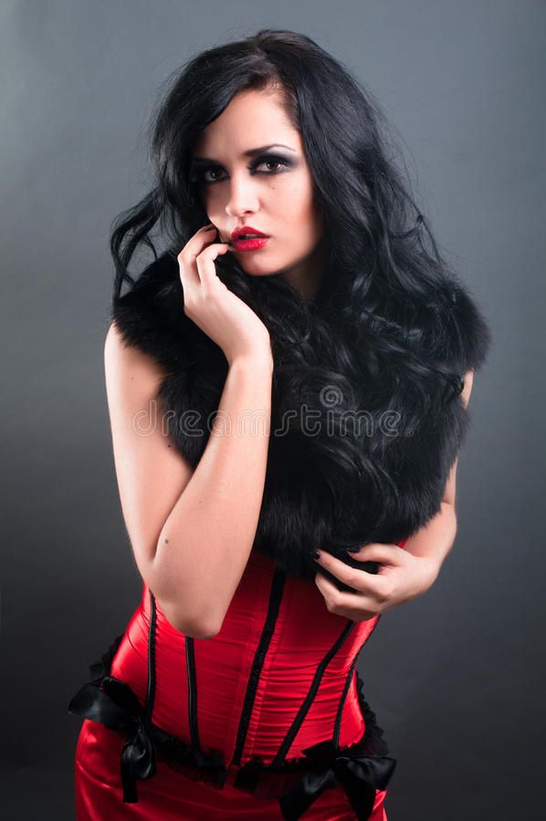 Brunette in red corset fur and long hair. Brunette in red corset and black fur and long hair in studio royalty free stock photo
