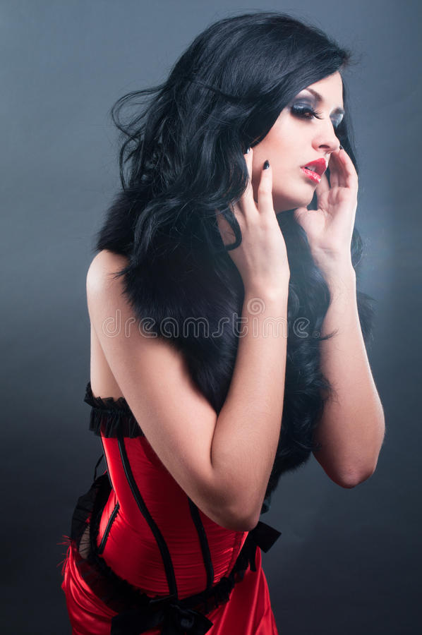 Brunette in red corset fur and long hair. In studio royalty free stock photography