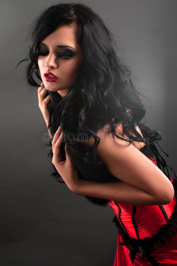 Brunette in red corset fur and long hair in s. Brunette in red corset and black fur and long hair in studio royalty free stock images